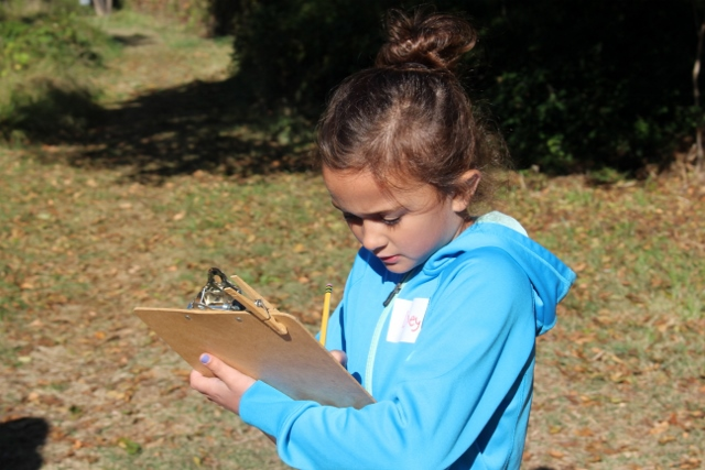 Child outdoors with clipboard