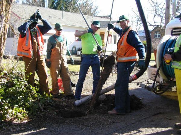 Crew removing roots in sewer line